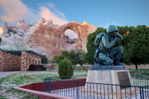 Photo of the Navajo Code Talker Monument in Window Rock, Arizona, with the Window Rock in the background.