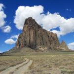 Photo of road leading up to Shiprock and Shiprock. Vertical.